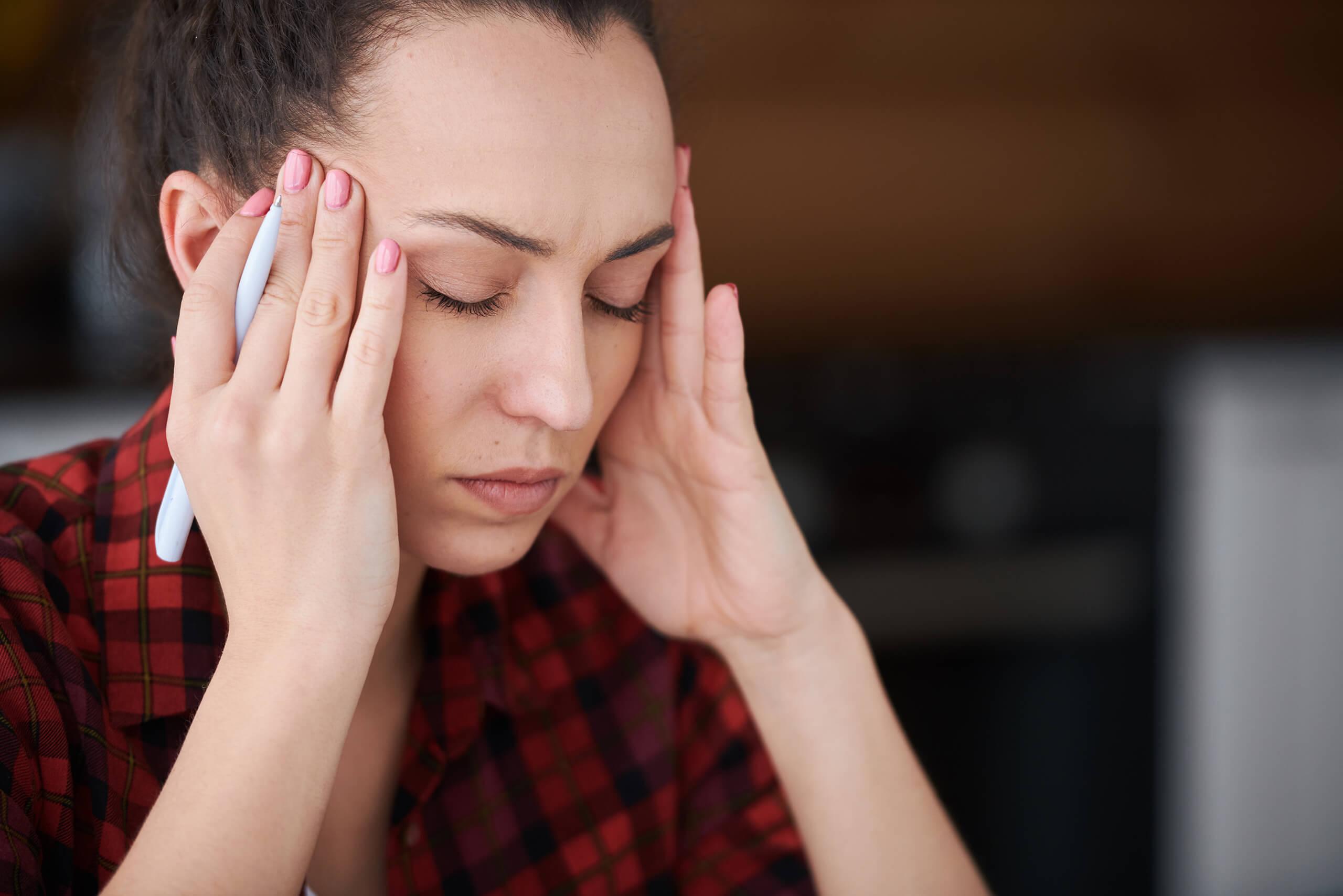 Frau mit Kopfschmerzen mit beiden Händen an der Schläfe