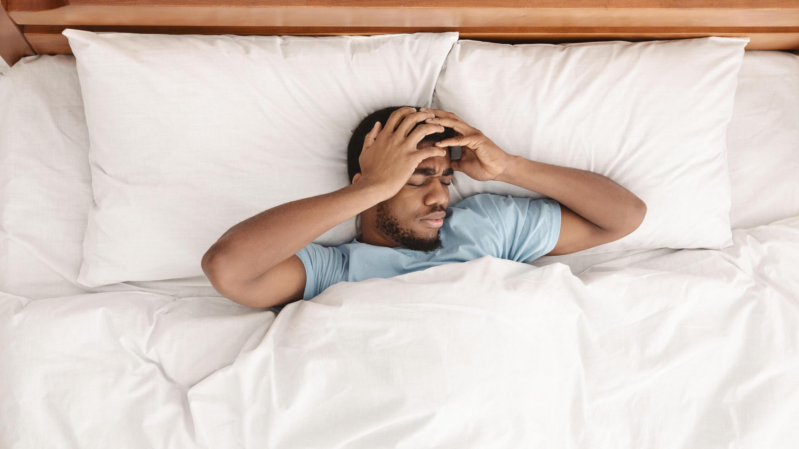 Ruheloser Mann mit Kopfschmerzen im Bett